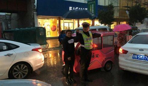 Wanita Dipuji, Payungkan Polis Bertugas Ketika Hujan Lebat