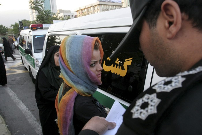 Morality police take down the name of a detained woman during a crackdown on